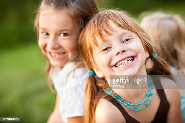 three happy sisters laughing while sitting together outside - redhead girl stock photos and pictures