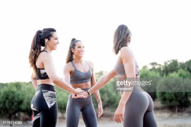 three happy sporty women stacking their hands after doing sports - coluna de madeira - fotografias e filmes do acervo