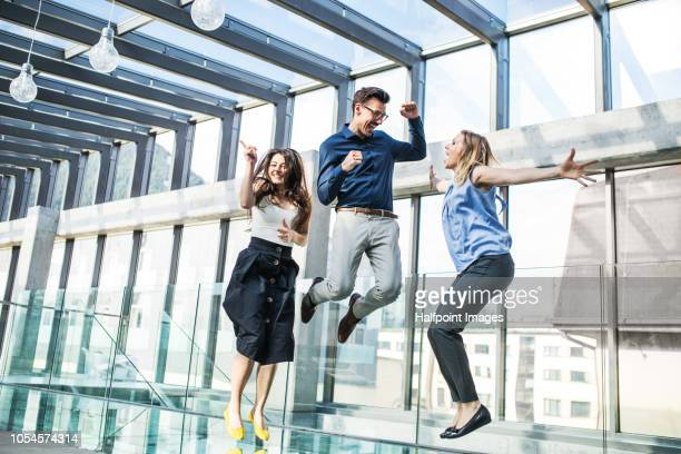 Three happy sucessful young business people expressing excitement.