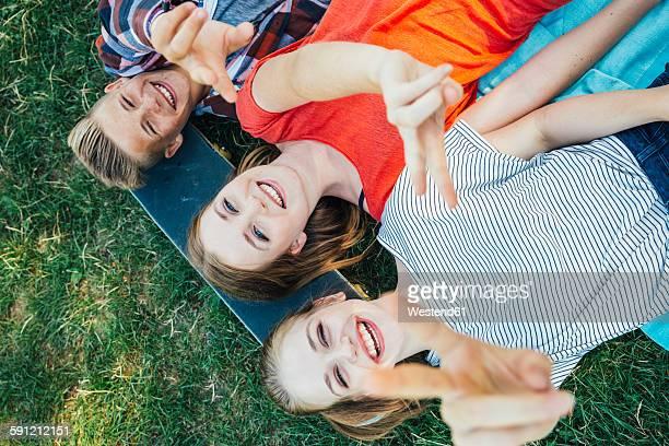 Three happy teenage friends lying on skateboard in meadow making victory sign
