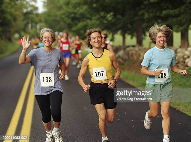 three happy women running in road race - marathon stock pictures, royalty-free photos & images