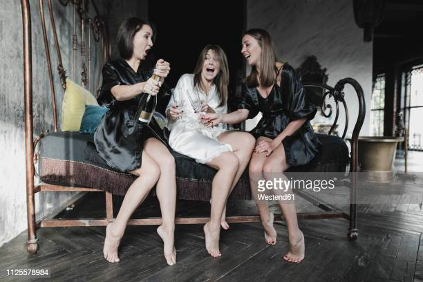 three happy women sitting on bed drinking champagne together - woman open legs stock photos and pictures