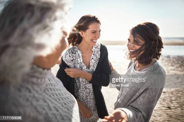 three happy women talking on the beach - three people stock pictures, royalty-free photos & images