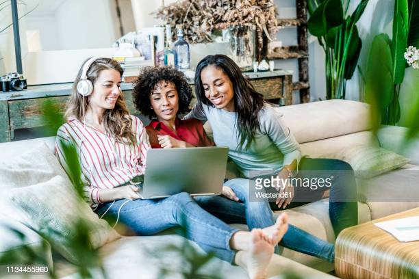 three happy women with laptop sitting on couch - seulement des adultes photos et images de collection
