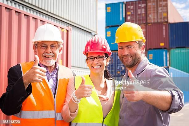 Três trabalhadores felizes no recipiente grande porto, parabéns!