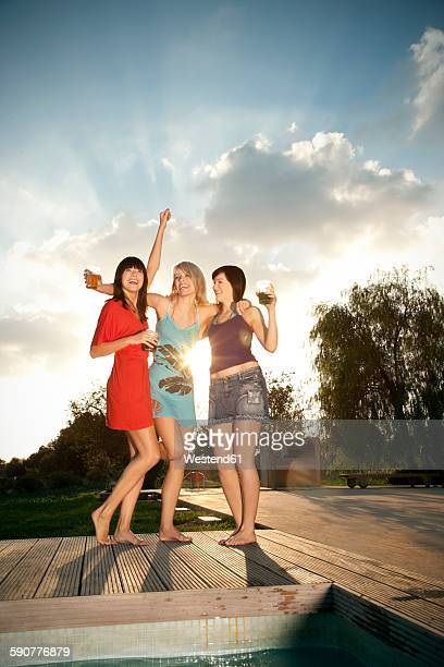 Three happy young women having a party at the poolside