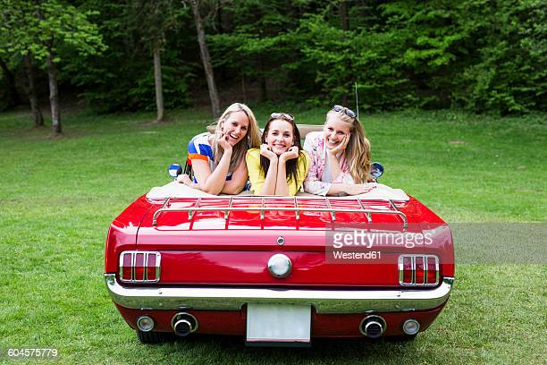 Three happy young women in a convertible parked on e meadow