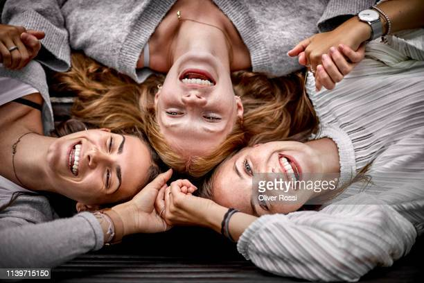 three happy young women lying on a bench holding hands - nur frauen stock-fotos und bilder