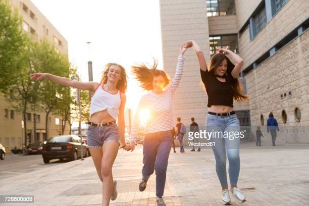 Three happy young women running hand in hand on sidewalk