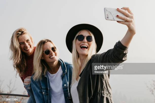 three happy young women taking a selfie outdoors - selfie stock-fotos und bilder
