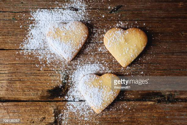 Three heart-shaped shortbreads sprinkled with icing sugar on wood