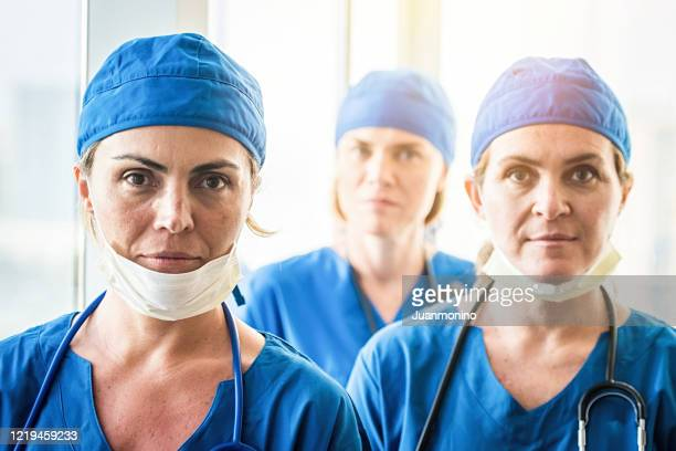 three heroes, tired overworked healthcare female workers very concerned and sad - heroes stock pictures, royalty-free photos & images