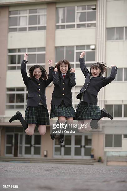 Three high school girls jumping in schoolyard
