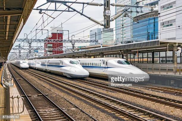 Three high-speed trains in station, two passing, one waiting for passengers