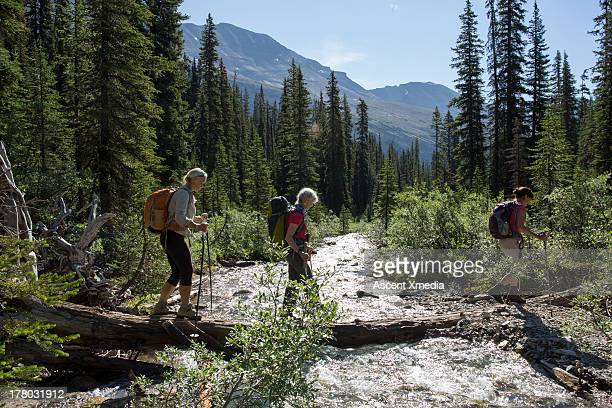 Three hikers cross mountain stream on log