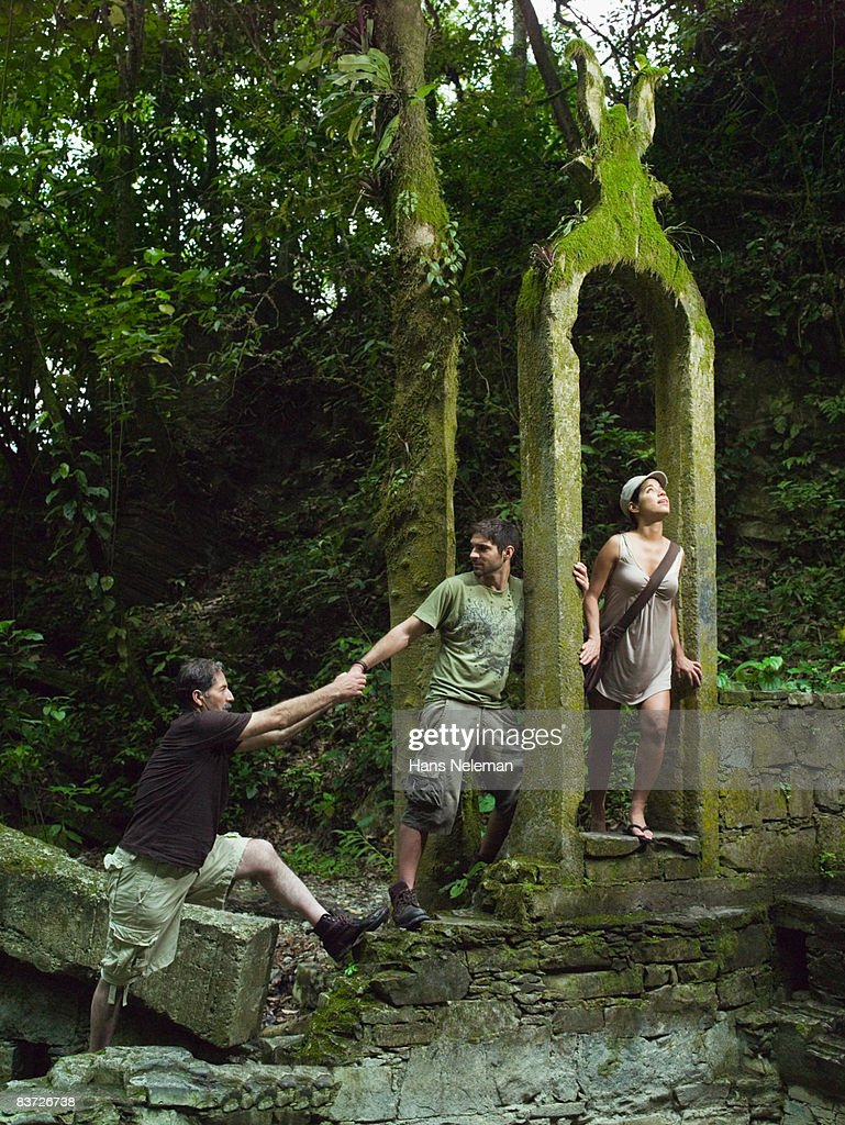 Three hikers exploring in jungle : Stock Photo
