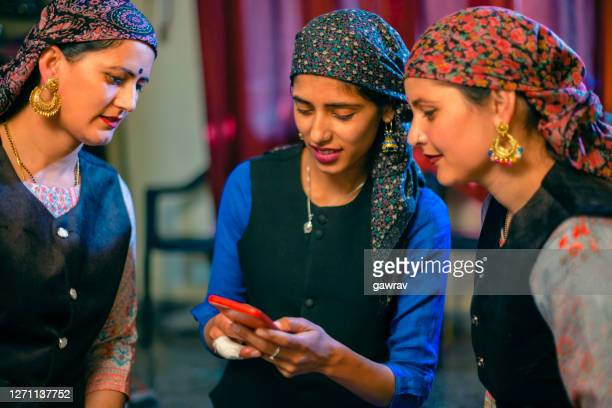 three himachali, beautiful young women share a smartphone together. - salwar kameez stock pictures, royalty-free photos & images