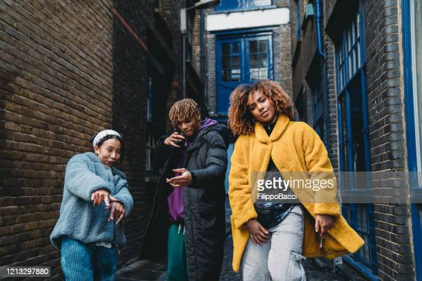 three hip friends dancing together outdoor in the city - hip hop music stock pictures, royalty-free photos & images