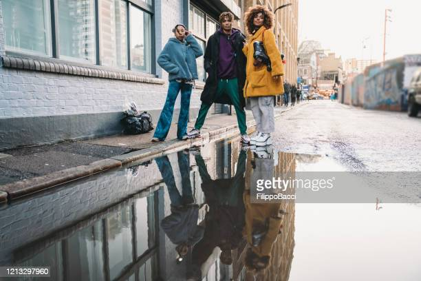 three hip friends reflected in a puddle in the city - hip hop music stock pictures, royalty-free photos & images