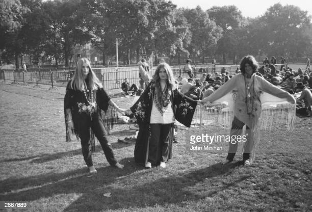 Three hippies wearing fringed shawls holding hands at a pop concert in Hyde Park London