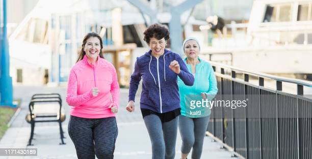 three hispanic women jogging in the city - 50 59 years stock pictures, royalty-free photos & images