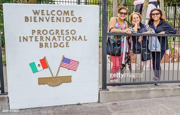 Three hispanic women on bridge between USA and Mexico