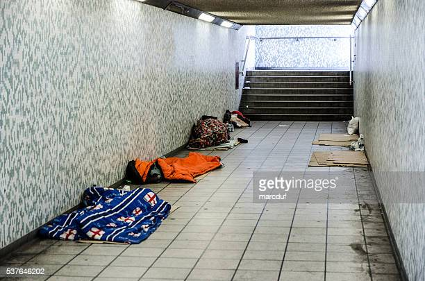 three homeless people sleeping in sleeping bag in a tunnel - imbalance stock pictures, royalty-free photos & images