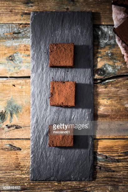three homemade brownies on slate - chocolate cake above stock pictures, royalty-free photos & images