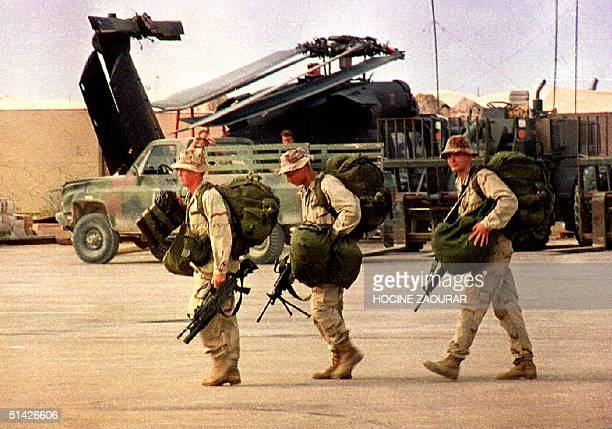 Three homeward bound US Army Rangers carry their bags and M16 rifles toward a military transport plane at Mogadishu International airport 21 October...