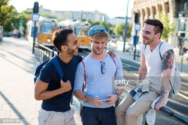 three homosexual men going to festival in summer - only young men stock pictures, royalty-free photos & images