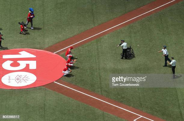 Three Honourable Members of the Canadian Armed Forces throw out the opening pitches on Canada Day on the 150th anniversary of the founding of the...