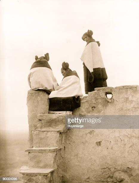 Three Hopi women at top of adobe steps New Mexico