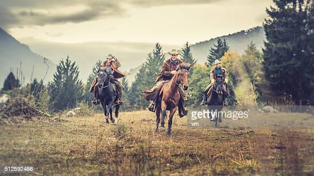 Trois randonneurs à cheval au galop sur un champ