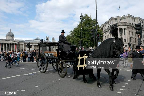 Three horsedrawn hearses carrying three symbolic adult coffins during the demonstration Cyclists participated in a funeral procession through central...