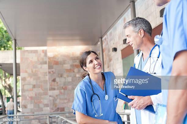 Three hospital workers standing in corridor