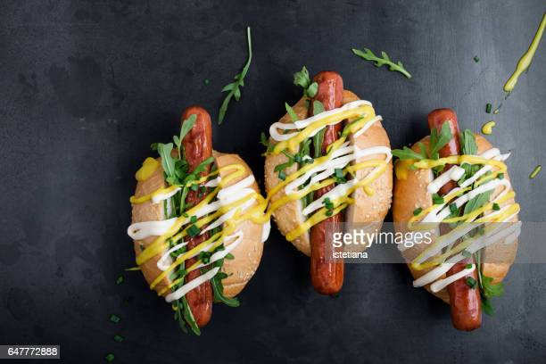 Three hot dogs with mustard, mayonnaise and arugula