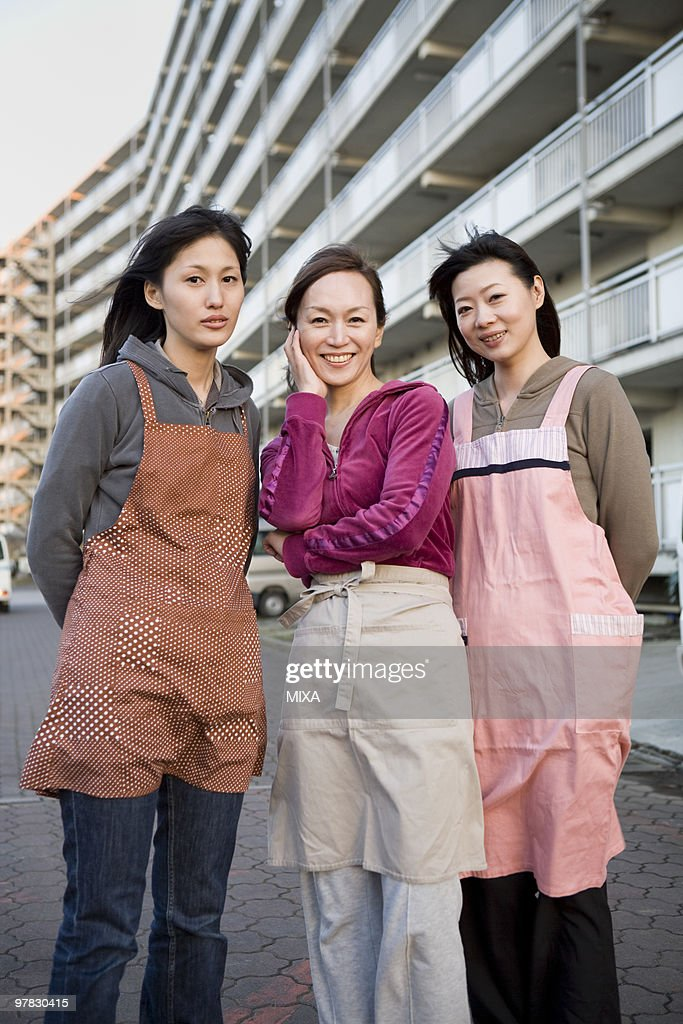 Three housewives standing in front of housing complex : Stock Photo