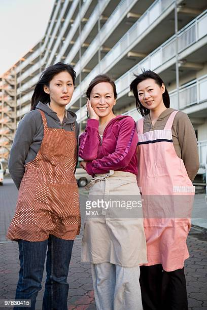 three housewives standing in front of housing complex - homemaker stock pictures, royalty-free photos & images