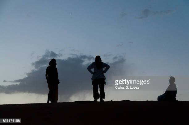 Three human figures in the Sahara Desert at dusk