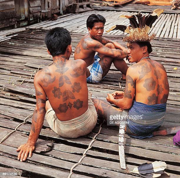 Three Iban Dayak men sitting on the deck of a longhouse East Malaysia Malaysia