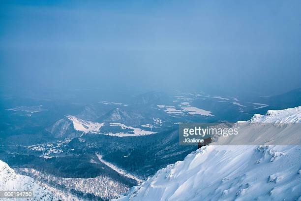 three ice climbers scaling a mountains summit - tottori prefecture stock photos and pictures