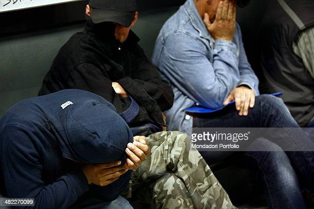 Three immigrants without the proper papers try to covers their faces with the hand or with their clothes in a room in which they're waiting to be...