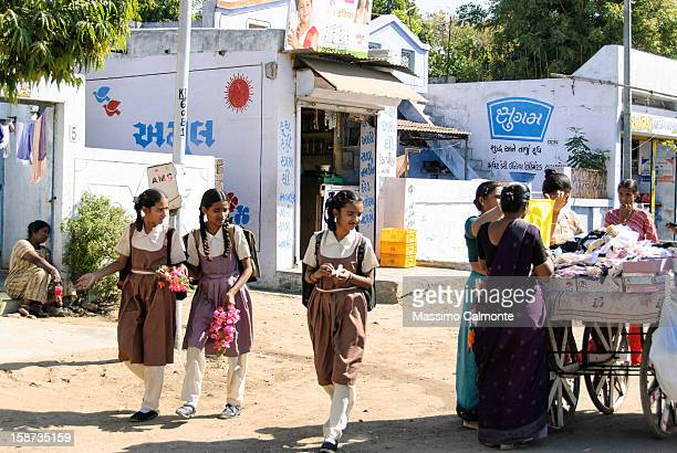 Three Indian schoolchildren walking back from school in Ahmedabad and observing a small street market