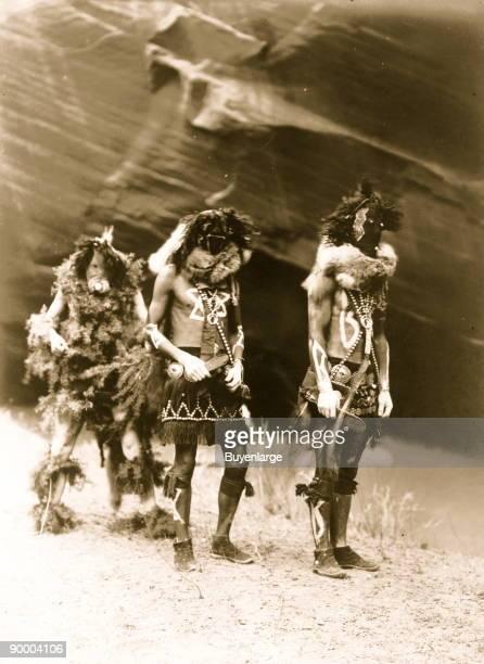 Three Indians Tonenili Tobadzischini and Nayenezgani in ceremonial dress photographed against dark rock background