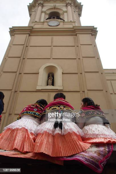 Three indigenous girls wearing typical costume sitting in front of the cathedral tower when hundreds of Quechuaspeaking Indigenous people devotees of...