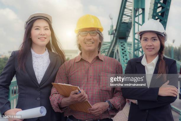 three industrial engineer wear safety helmet engineering working and talking with drawings inspection on building outside. - 将校 ストックフォトと画像