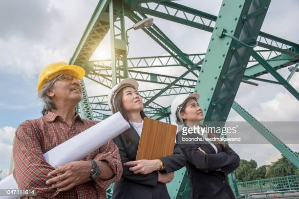 three industrial engineer wear safety helmet engineering working and talking with drawings inspection on building outside. - general military rank stock pictures, royalty-free photos & images