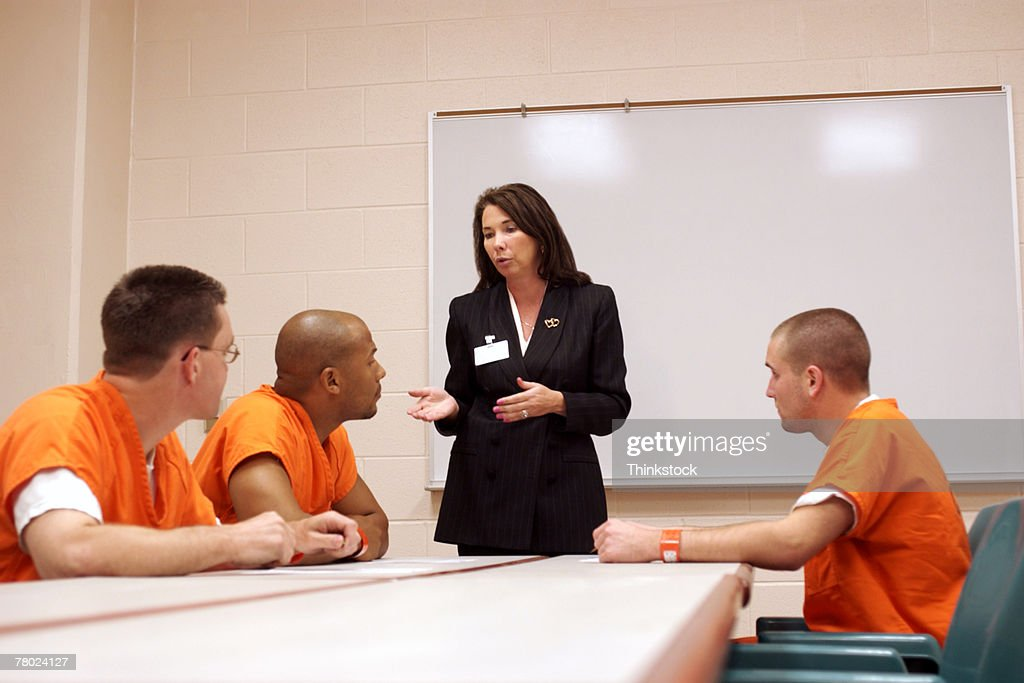 Three inmates listen to a woman discuss options and privileges that they might earn while serving time in prison. : Stock Photo