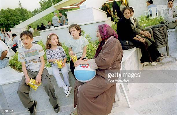 Three Iranian children eat potato chips while sitting with their grandmother June 14 2001 at the concession stand in Park Mellat in northern Tehran...