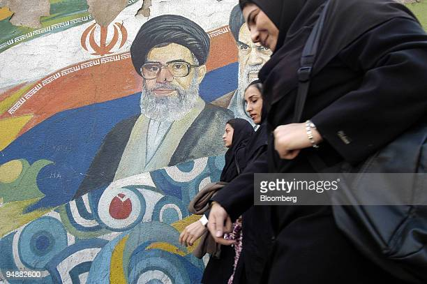 Three Iranian women pass a wall mural depicting Ayatollah Khomeini and Ayatollah Khamenei in Tehran Iran Thursday February 26 2004 BNP Paribas SA and...